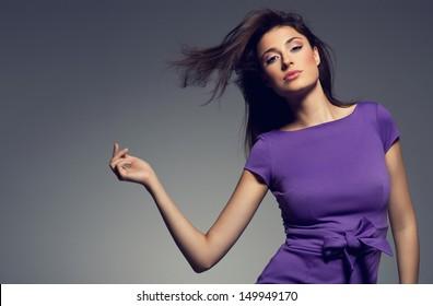 portrait of beautiful woman wearing purple dress. studio shoot.
