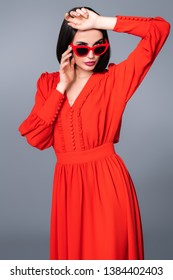 A portrait of a beautiful woman wearing red dress and sunglasses. Fashion, style, beauty, optics.