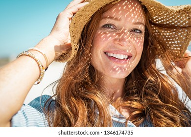 Portrait of beautiful woman wearing straw hat with large brim at beach and looking at camera. Closeup face of attractive smiling girl with freckles and red hair. Happy mature woman enjoying summer.