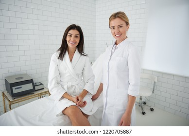 Portrait of beautiful woman in white bathrobe sitting on daybed while beautician standing beside her. Ladies looking at camera and smiling