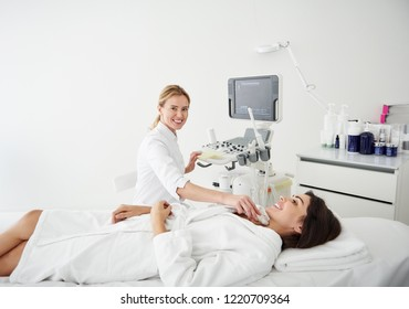 Portrait of beautiful woman in white bathrobe lying on daybed during medical examination at wellness center
