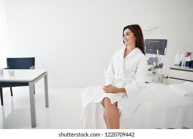 Portrait of beautiful woman in white bathrobe sitting on daybed. She is looking away and smiling
