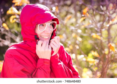 portrait of beautiful woman with white big glasses in red coat