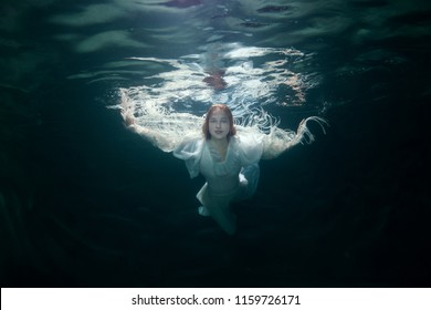Portrait of a beautiful woman in a white dress under the water.