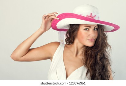 Portrait of a beautiful woman in a white hat from the sun.