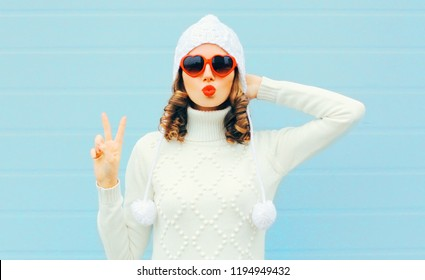 Portrait beautiful woman in white knitted sweater, hat, sends air kiss on blue background