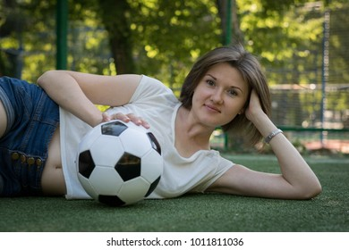 Portrait of a beautiful woman in white t-shirt and jeans shorts posing with a soccer ball