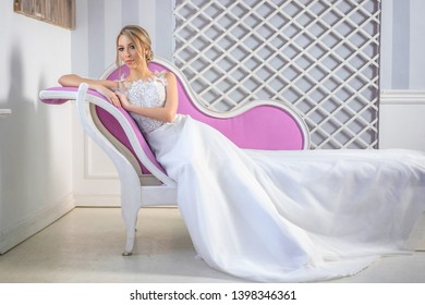 portrait of a beautiful woman in a white wedding dress with a beautiful make-up and hair on the couch