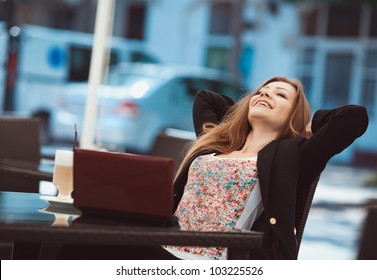 Portrait of beautiful woman in winning pose and smiling sitting in a cafe with laptop outdoor