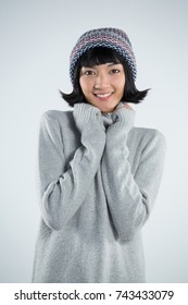 Portrait of beautiful woman in winter clothing posing against white background