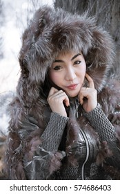 Portrait of beautiful woman in winter cloths at pine forest