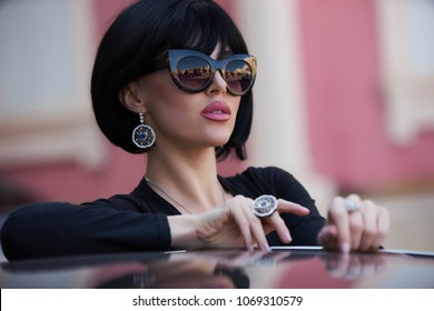 Portrait of a beautiful woman with yellow sports car outdoor . Young rich slim girl driver . Lady with black hair wearing sunglasses Spring-summer