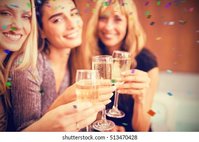 Portrait of beautiful women holding drinks against flying colours