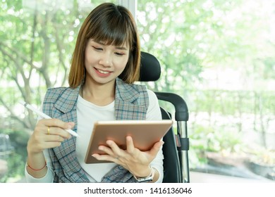 Portrait of beautiful working woman using tablet with smart pen with happy.
