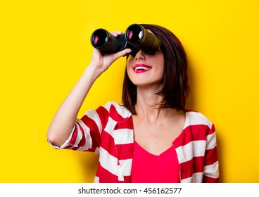 portrait of the beautiful yound woman with binoculars on the yellow background