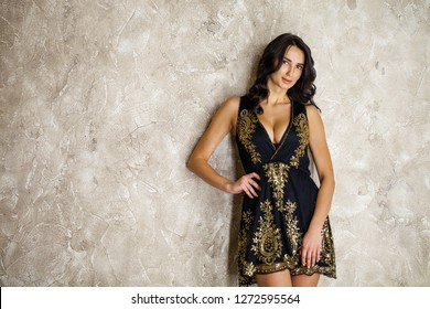 Portrait of beautiful young adult attractive sexy and sensuality pretty brunette woman in black elegance fashionable dress on gray studio wall background