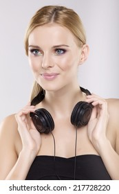 portrait of beautiful young adult sensuality attractive and pretty blonde woman is listen to the music on the headphones