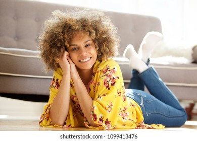 Portrait of beautiful young african american woman lying on floor at home