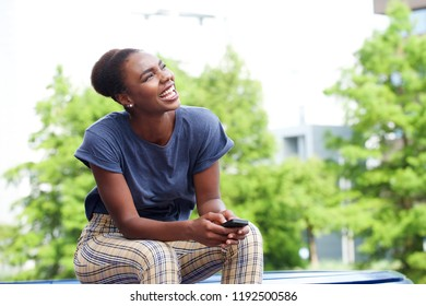 Portrait of beautiful young african american woman laughing with mobile phone outdoors