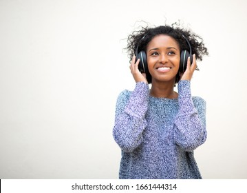 Portrait beautiful young african american woman smiling with headphones against white background