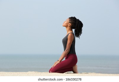 Portrait of a beautiful young african american woman meditating at the beach enjoying summer