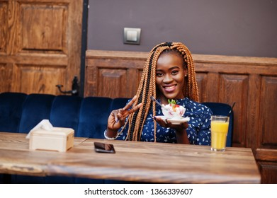 Portrait of beautiful young african business woman with dreadlocks, wear on blue blouse and skirt, sitting in cafe with ice cream and pineapple juice. She show two fingers.