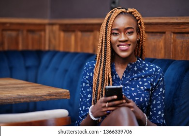 Portrait of beautiful young african business woman with dreadlocks, wear on blue blouse and skirt, sitting in cafe with mobile phone.