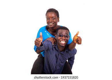 portrait of a beautiful young African couple, man holding his girlfriend on his back and showing their thumbs up together while smiling.