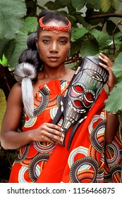 Portrait of a beautiful young African woman sitting outside with foliage in the background wearing traditional clothing and holding a mask