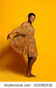 Portrait of a beautiful young African woman over yellow background. Studio picture