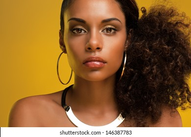 Portrait of a beautiful young African woman wearing gold jewelry.