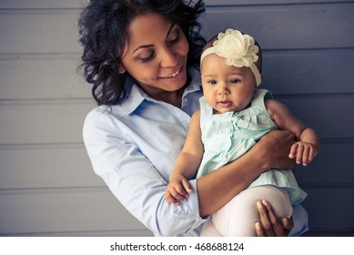 Portrait of beautiful young Afro American mother holding adorable little baby girl in her arms, looking at her and smiling, standing on gray background