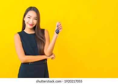 Portrait schöne junge asiatische Geschäftsfrau mit Autoschlüssel auf gelbem Hintergrund