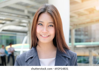 Portrait beautiful young asian business woman standing in front of office building in business area.