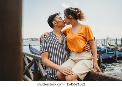 Portrait of a beautiful young Asian couple kissing on vacation in Venice, Italy, behind them the lagoon and gondolas - Millennial on their honeymoon -