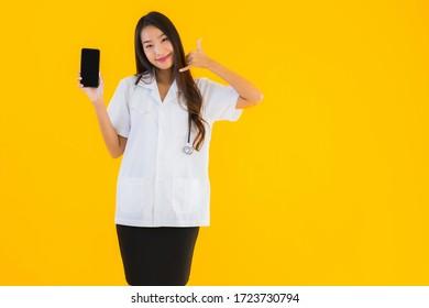 Portrait schöne junge asiatische Ärztin verwenden Smartphone auf gelbem isolierten Hintergrund
