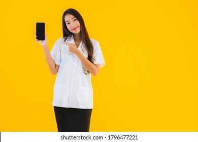 Portrait schöne junge asiatische Ärztin benutzt Smartphone auf gelbem, isoliertem Hintergrund