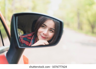 Portrait Beautiful young Asian girl  Smiling driver-woman is reflected in mirror of car.