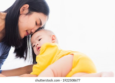 Portrait of beautiful young Asian mother kissing her infant newborn baby in a white bed, The mom loves his child, Healthcare and medical and mother day concept