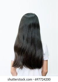 Porträt eines schönen jungen asiatischen Teenagermädchens mit langen, schwarzen Haaren. Rückansicht von Kindern mit trockenem Haar auf weißem Hintergrund. Haarschäden, Gesundheits- und Schönheitskonzept.