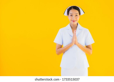 Portrait beautiful young asian thai nurse sawasdee or say hello in Thai on yellow isolated background
