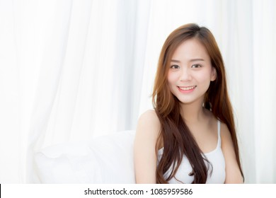 Portrait beautiful young asian woman standing and smile the window at bedroom while wake up with sunrise at morning, lifestyle and relax concept.