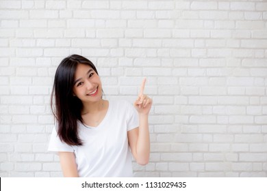 Portrait beautiful young asian woman happiness standing finger pointing something on gray cement texture grunge wall brick background, businesswoman is a smiling on concrete, business people concept.