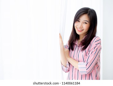Portrait of beautiful young asian woman standing the window and smile while wake up with sunrise at morning, lifestyle and relax concept.