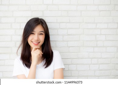Portrait of beautiful young asian woman happiness standing on gray cement texture grunge wall brick background, businesswoman is a smiling on concrete, business people concept.