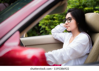 A portrait of a beautiful young asian woman wearing glasses and she is in the red car