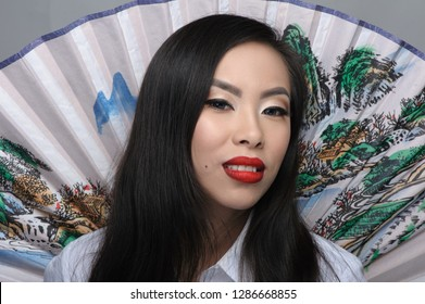 Portrait of beautiful young asian woman with fan on background