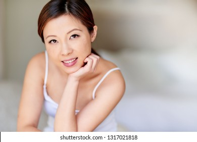 Portrait of a beautiful young Asian woman with a perfect complexion sitting at home in the morning with her hand on her chin