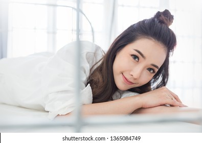 Portrait of beautiful young asian woman with attractive smile enjoy fresh soft bedding linen mattress in white bed room modern apartment. Teenage girl resting, good night sleep concept.
