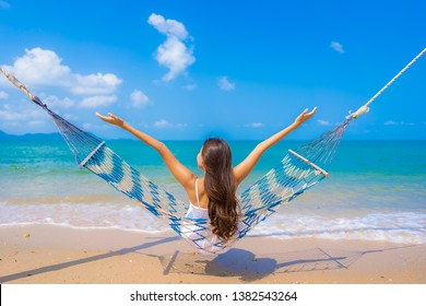 Portrait beautiful young asian woman happy smile leisure on hammock swing around the beach sea and ocean with blue sky white cloud for vacation travel